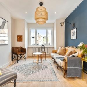 couleur mur salon décoration canapé retro style lampadaire rotin fauteuil cuir pieds métal tapis franges