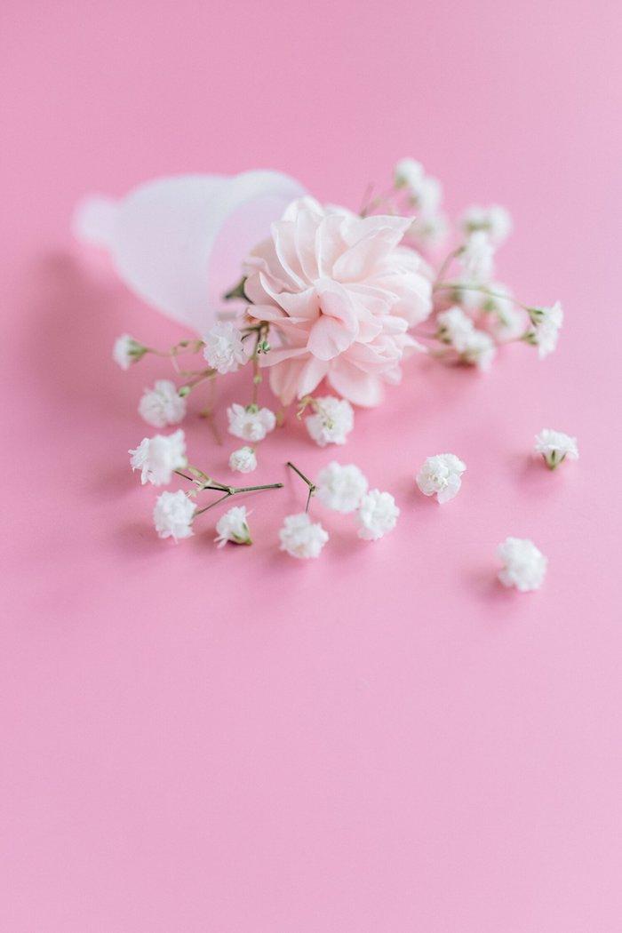coupe menstruelle blanche une fleur rose dedans et brins de muguet persemés