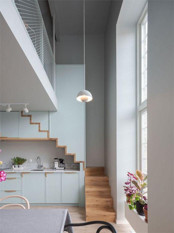cuisine bleu pastel sous mezzanine escalier bois meuble cuisine original table entourée de chaises noires et blanches