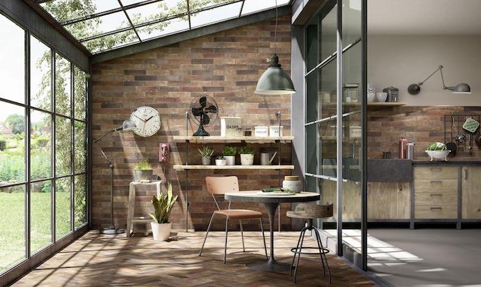 cuisine dans une véranda séparé avec un mur veriier des avec une petite table ronde et horloge accroché