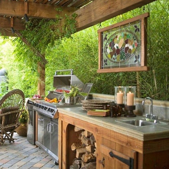cusine dans une véranda derrière un mur de verdure une barbecue et art verrièer ppendant