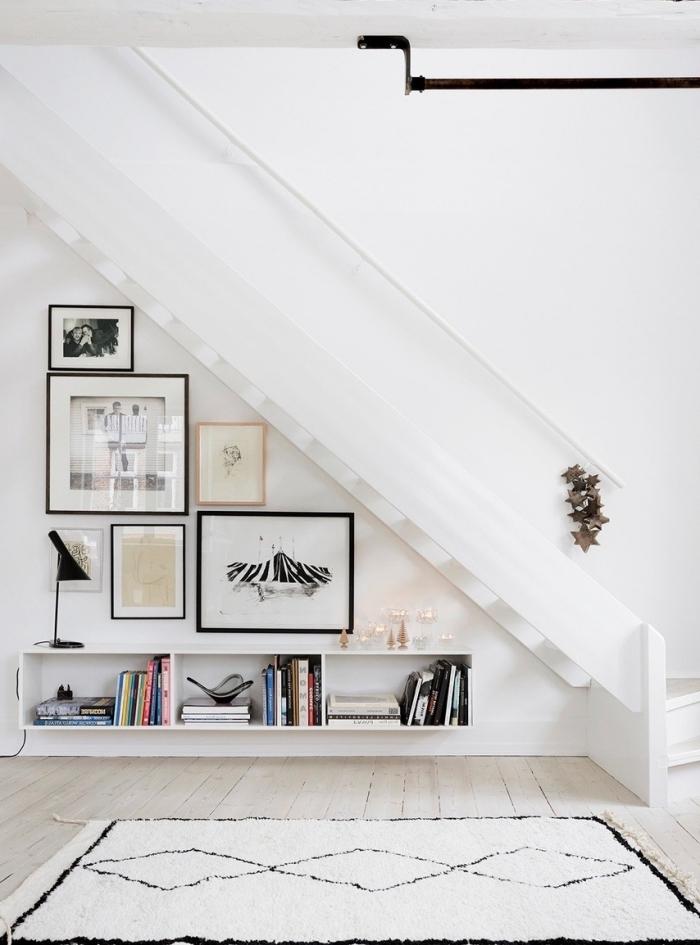 décoration minimaliste mur de cadres meuble rangement sous escalier tapis blanc et noir
