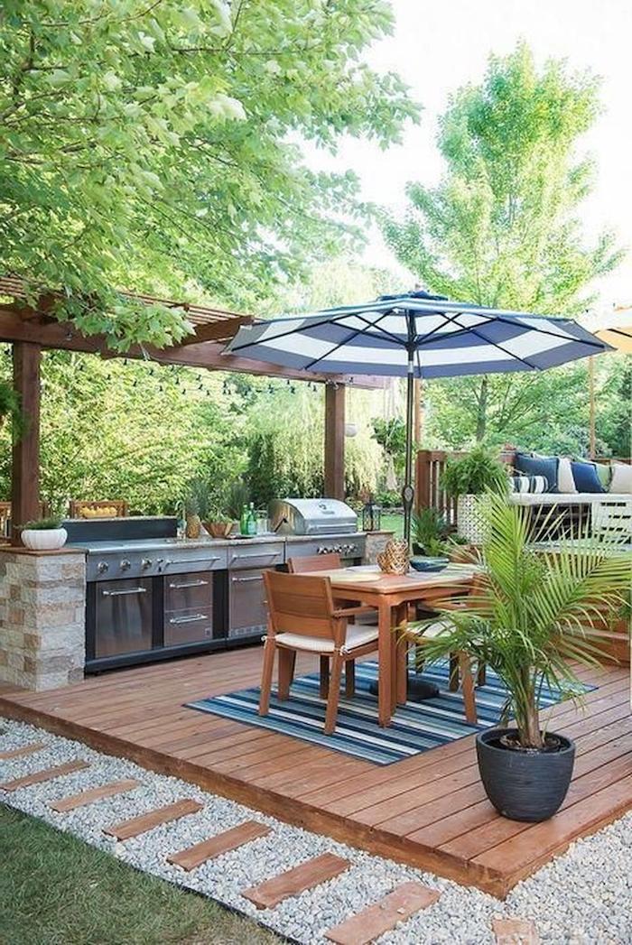 deco veranda cocooning entourée des arbres avec des allées en cailloux et des parasols
