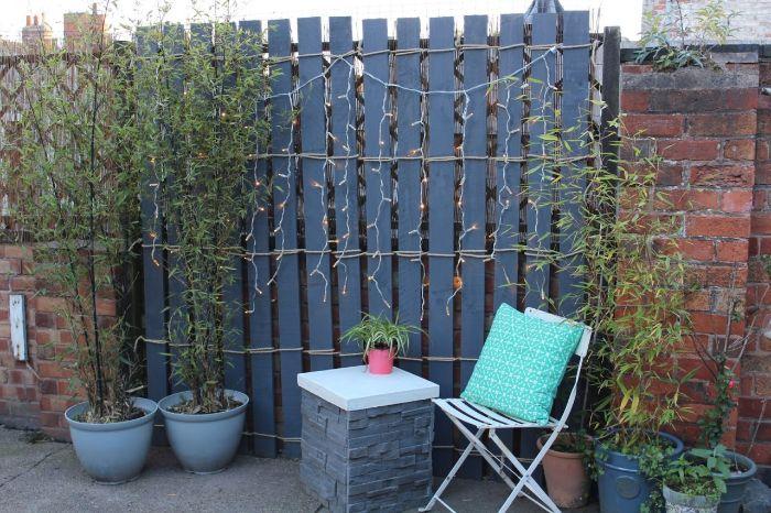 decoration cour de jardin avec separation de barriere en palette repeinte de bleu avec guirlande lumineuse
