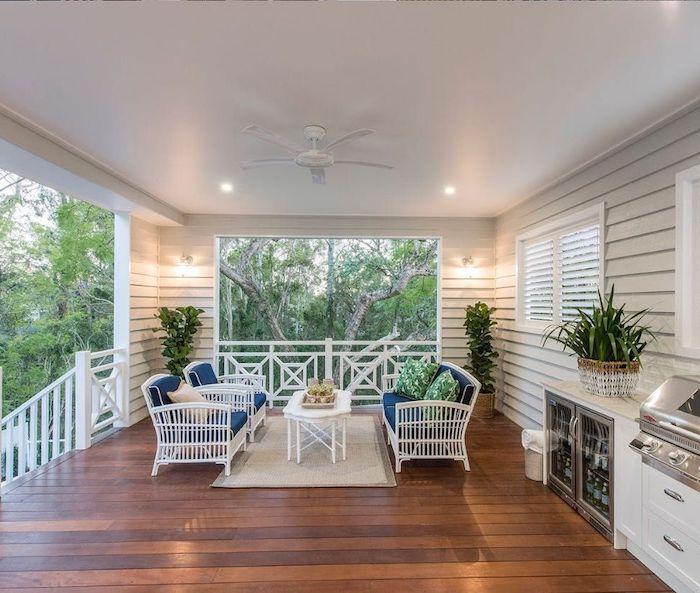des chaises blanches et une table basse sur un sol en bois foncé idée deco veranda