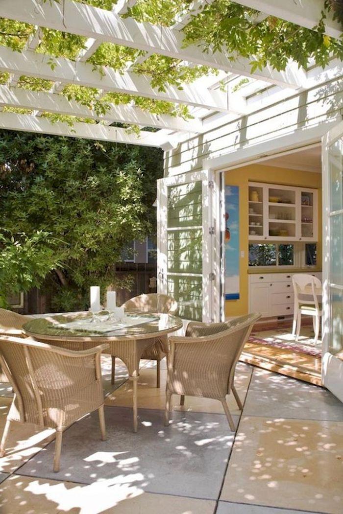 des chiases en raton autour d une table ronde sous un toit de verdure dans une extension cuisine