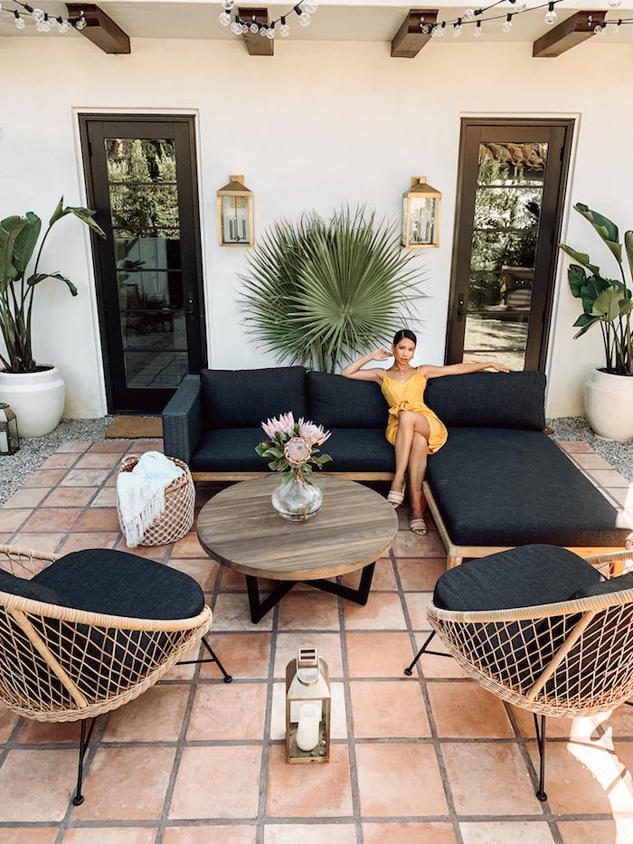 des fauteuils et un canapé grand en rotin dans une véranda une femme assise vetue en robe jaune