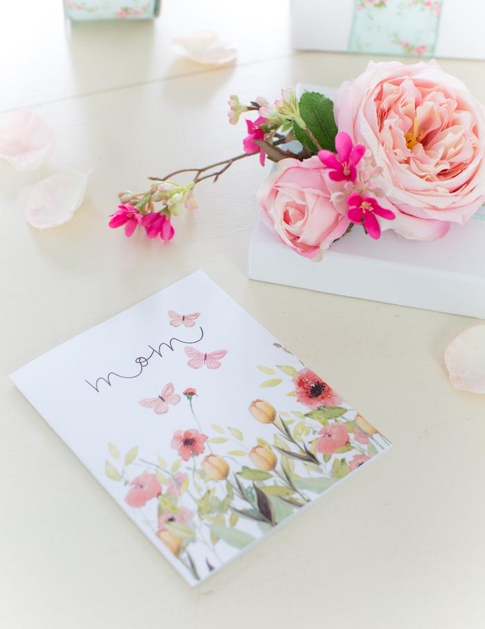 des fleurs artificiels sur un table a coté d d un carte fête des mères