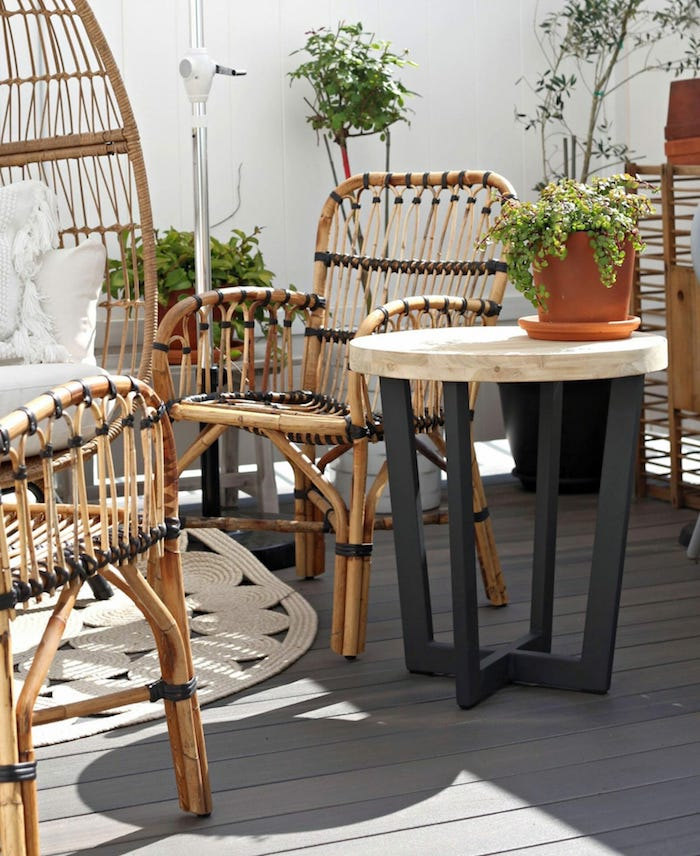 des meubles en rotin dans une véranda avec des details teints en noir