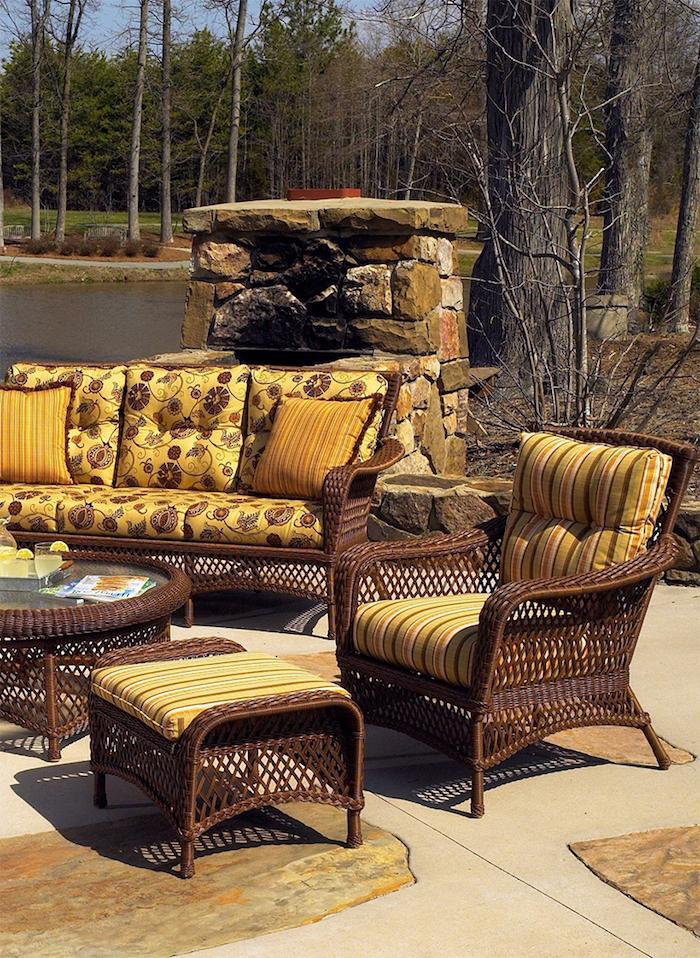 des meubles marrons avec des coussins jaunes a motis devant une cheminée en pierre