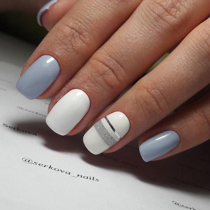 des ongles teint en vernis pastel blanc et bleu avec des lignes en paillettes