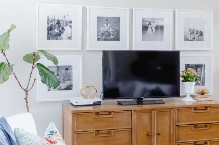 design deco mur derriere tv cadres mur photos blanc et noir meuble bois plante verte fauteuil blanc