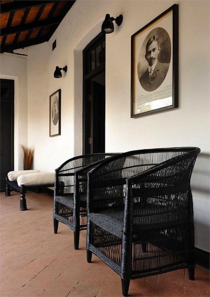 deux chaises en rotin tents en noir au dessous d un table avec la photo de ghandi