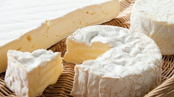 deux fromages camembert et brie dans un panier tissée couvert de la moisie