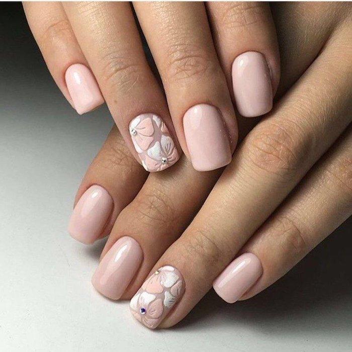 deux mains avec ongle en)gel pastel décoré)des fleurs et petites pierres