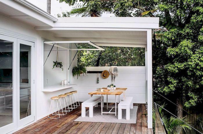 extension de la cuisine vers la véranda avec une table à langer et un fenetre de passage des repas