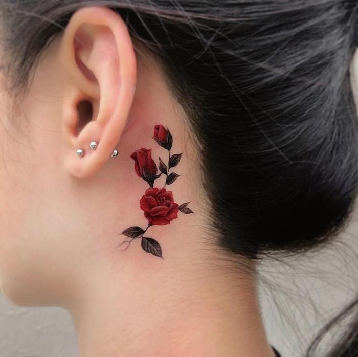 femme cehveux noirs avec tatouage fleur minimaliste derrièer l oreille