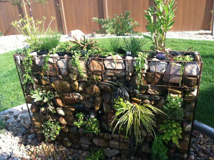 grand bac grille metallique aux pierres et plantes vertes pour separer et decorer un jardin