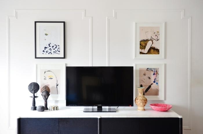 habillage du mur derrière tv platre déco cadres portraits femme peinture art mur statuettes