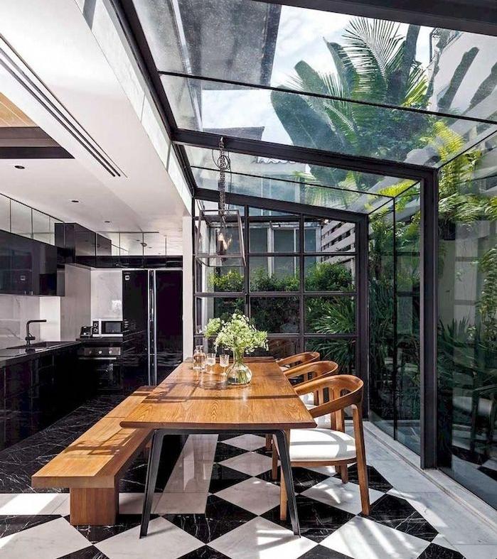 habillage mur intérieur veranda avec des outils de cuisiner derrière un mur en verre