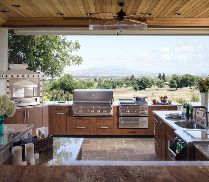 idée d aménagement veranda avec des outil pour cuisiner un four evier et grille ventilateur sur un plafond bois