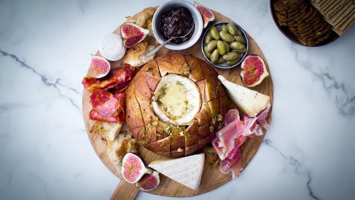 idéee de recette avec camembert dans un pain entourée de charcuterie olives et fruits sur une surface en marbre copy