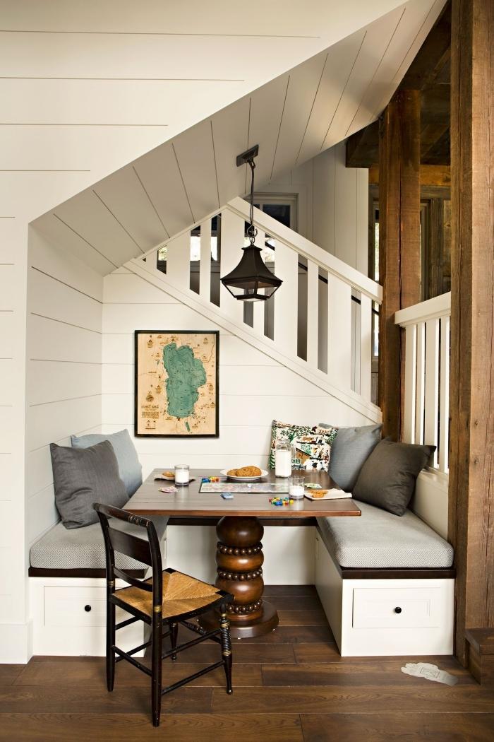 installation meuble sous escalier banquette bois foncé housse gris clair coussins décoratifs table bois foncé