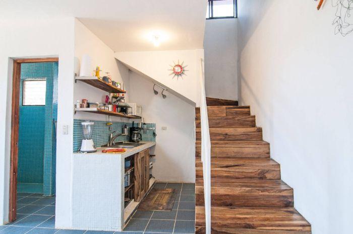 kitchenette blanche sous escalier avec portes de bois étagères bois ouvertes credence carrelage bleu