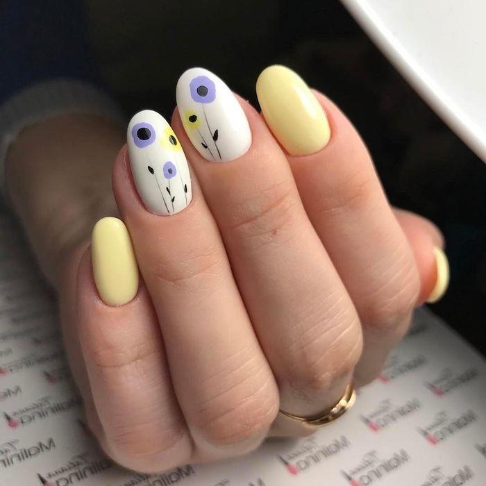 main feminine avec bague d orée et des ongle arc en ciel en)couleur pastel