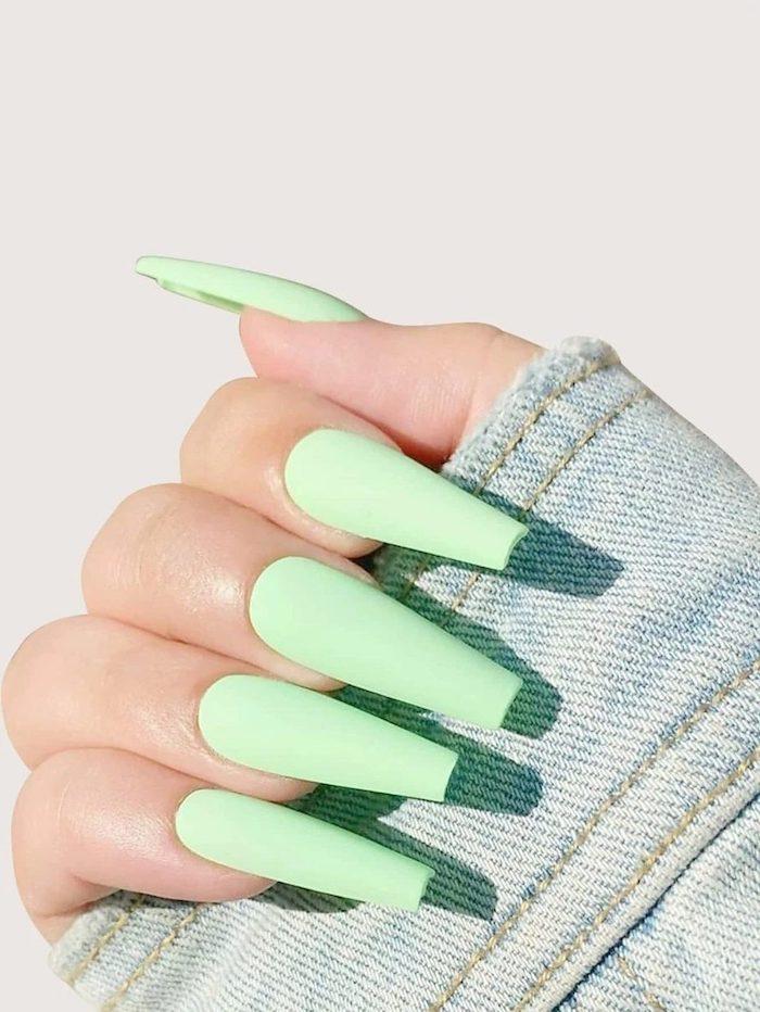 ongle vert pastel xtremement longues et un main avec veste en deni,