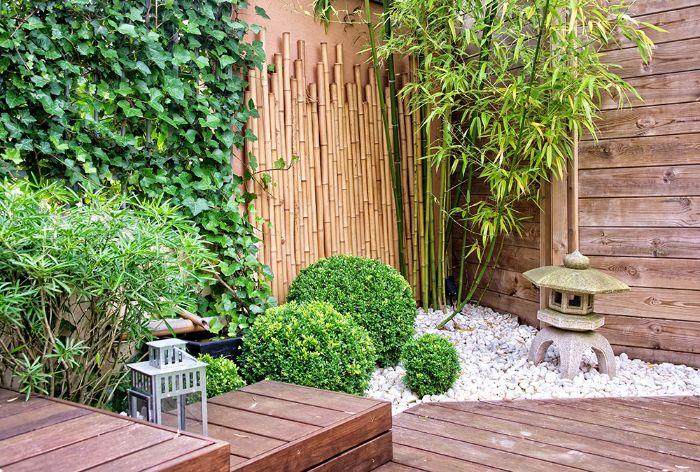 palissade bambou piquets buissons lierre et galets blancs dans un coin de jardin terrasse en bois composite