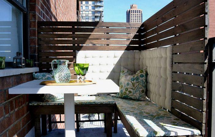 palissade en palette recyclée sur balcon aménagé avec des bancs de bois coussins et housses mur de briques