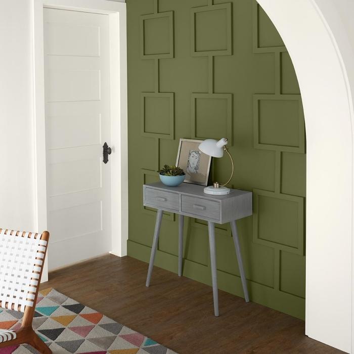 pan de mur revetement mural panneaux décoratifs peinture vert kaki tapis multicolore motifs triangulaires