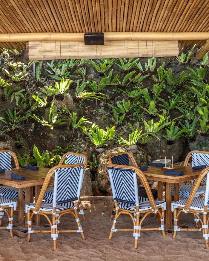 peindre des chaises en rotin en deux couleurs a rayures bleues sous un toit en bambou