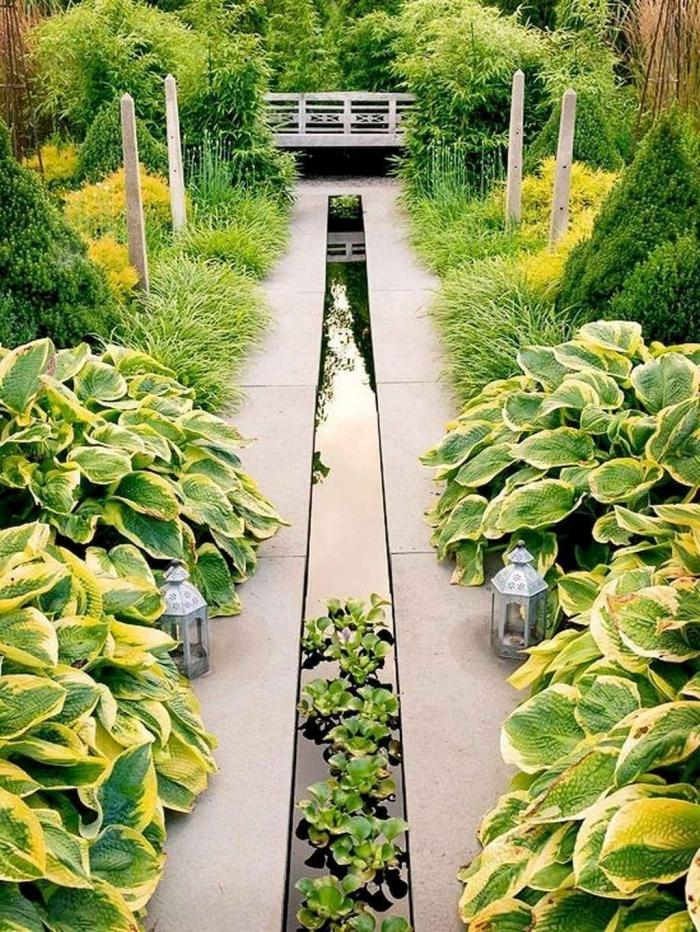petit jardin japonais zen petit bassin plantes vertes lanterne végétation haies cloture bambou