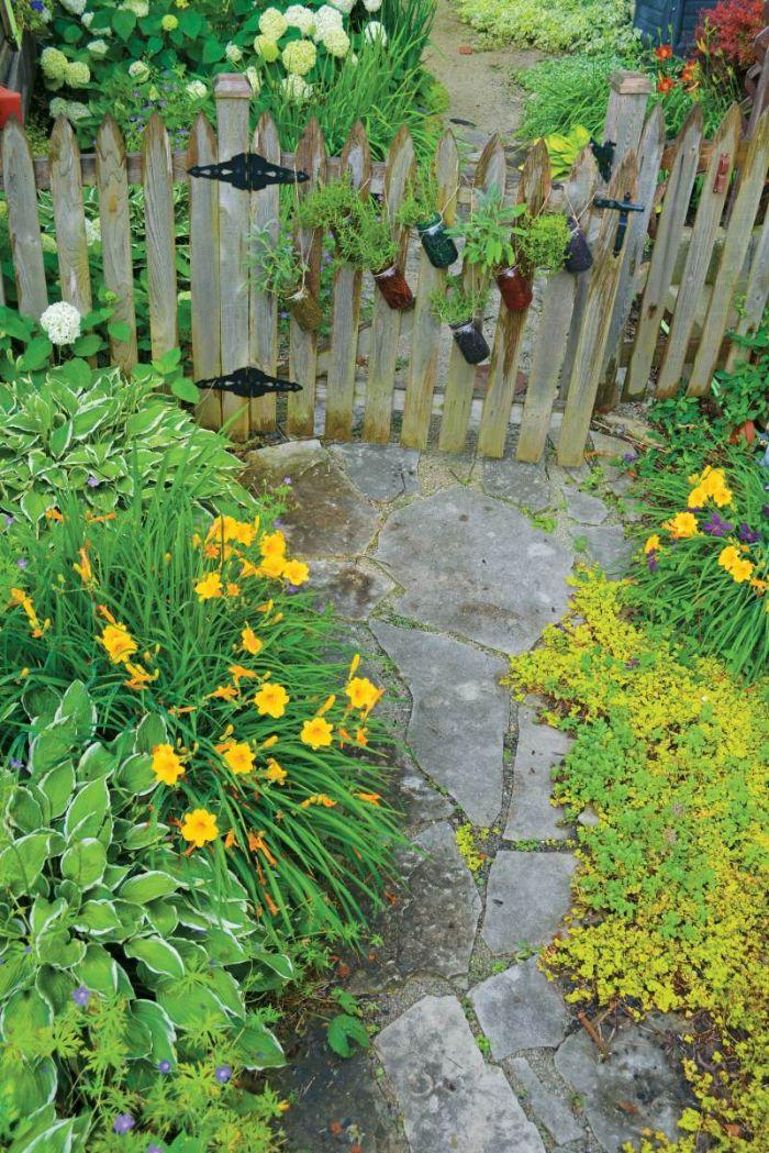 petite palissade de bois avec des pots en verre aux herbes aromatiques chemin de jardin en pierre et bordure de jardin fleurs et buis