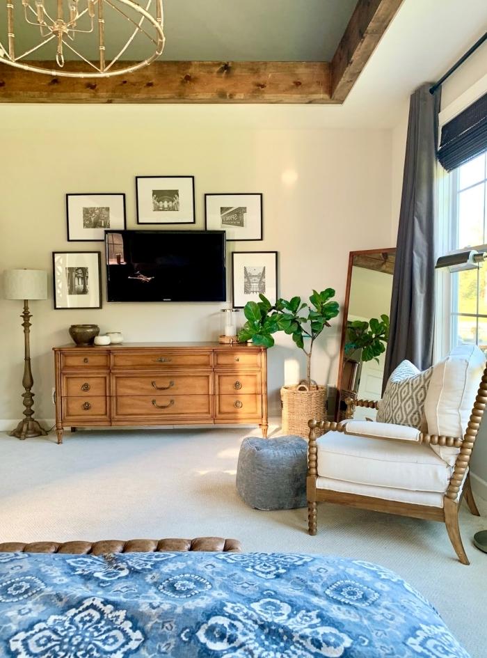 plafond suspendu poutres bois cache cable tv derriere mur de cadres photos blanc et noir fauteuil bois