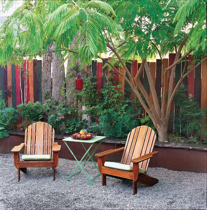 planches de bois recyclées et repeintes pour cloturer un jardin chaise longues de bois sur gravier
