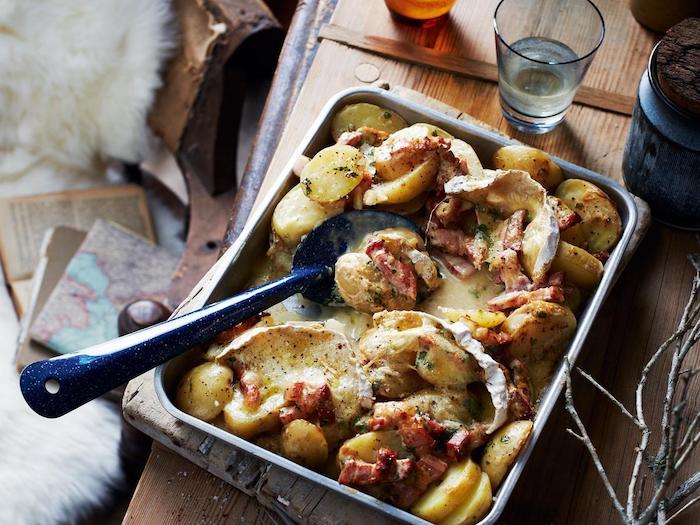 recette camembert au four lardons pomme de terre dans une plaque métallique sur une table en bois a coté d une verre d eau