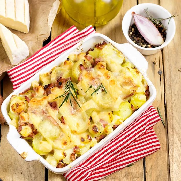 recette de tartiflette au camembert garni de romarin a coté d un bol rempli de poivre copy