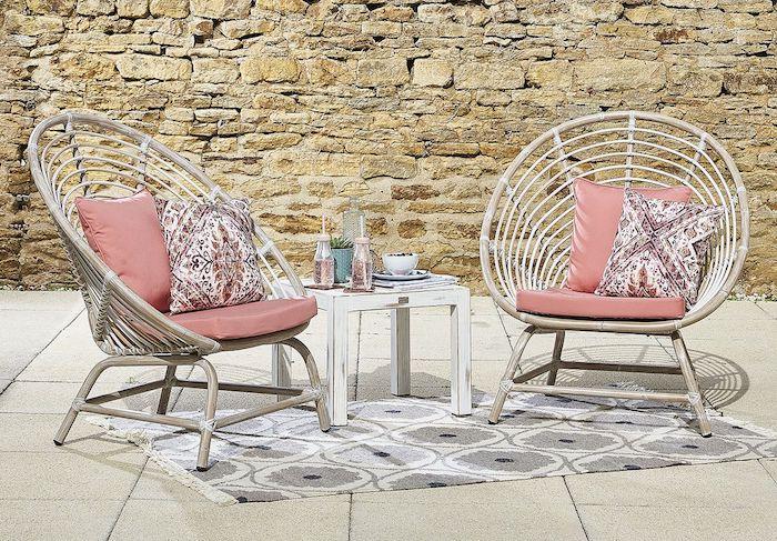 relooker un fauteuil enrotin avec des coussins décoratives roses devant un mur en briques