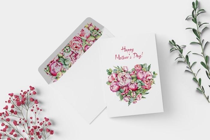 romarin et brin de baie a coté d une carte dans enveloppe pour la fête des mères