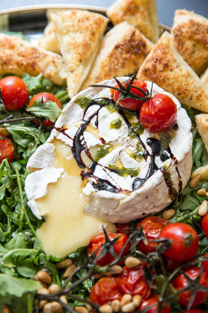 salade verte avec des tomates cerise des noix de cedre et un camembert chaud et fondu au dessus