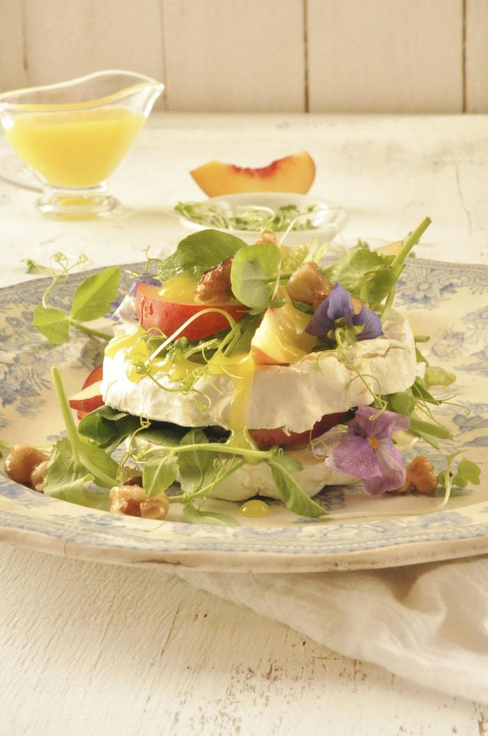 salalde composée originale avec des la roquete camembert et des fleurs comestibles un morceau de peche au fond