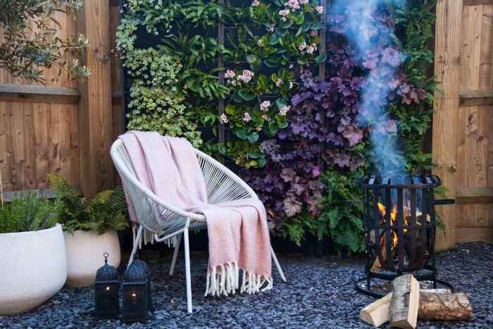 salon de jardin cocooning avec chaises en metale et couverture moelleuses gravier pots fleuris brise vue naturel