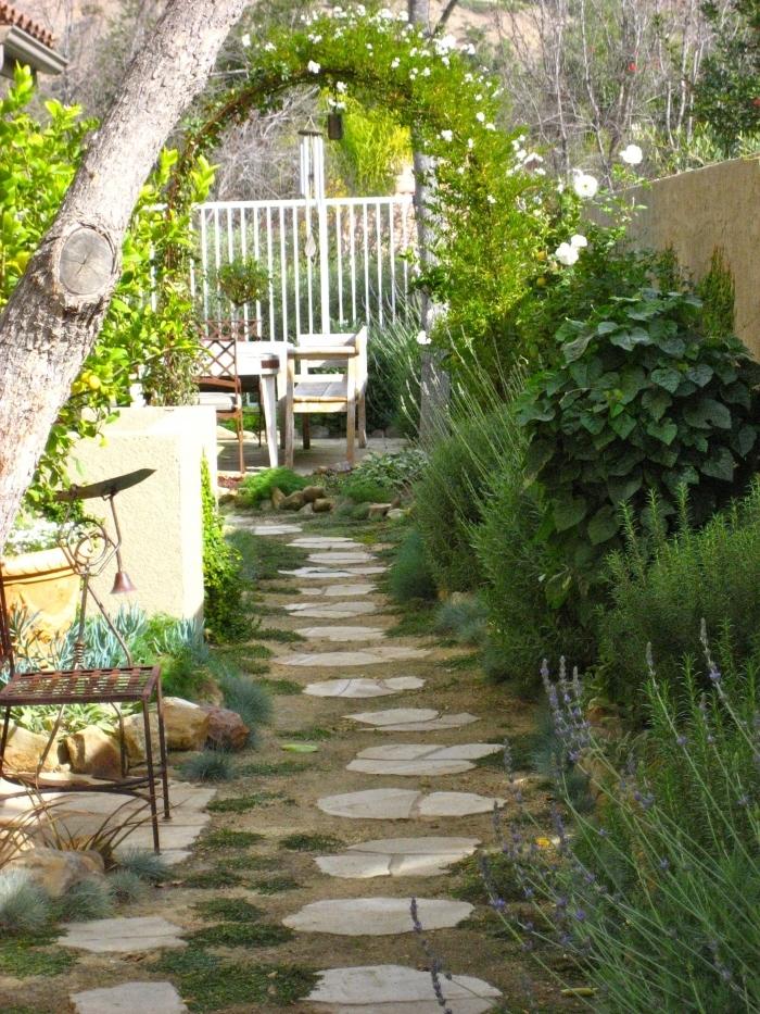 sentier dalles gazon arc végétal amenagement jardin simple cloture blanche meubles extérieur bois