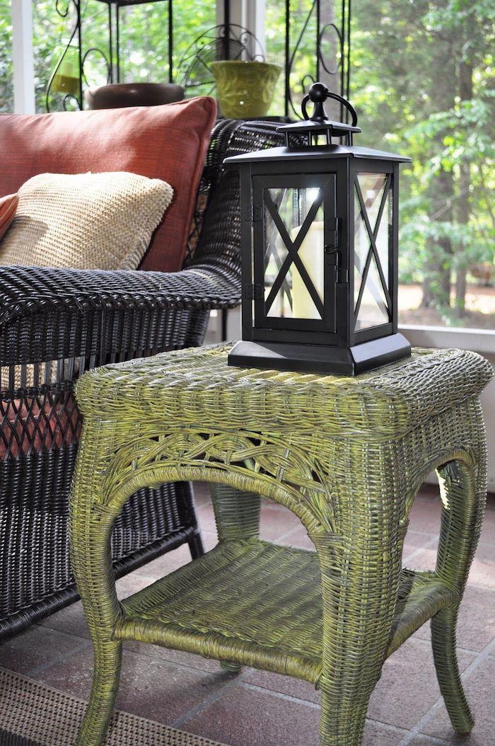 table de cehvet vintage relooké avec de la peinture verte une laterne au dessus et canapé en rotin noir