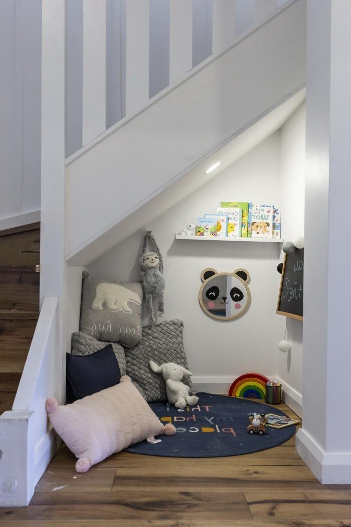 tapis rond étagère bois blanc aménagement sous escalier ouvert coussins gris jouets coin de jeux couloir