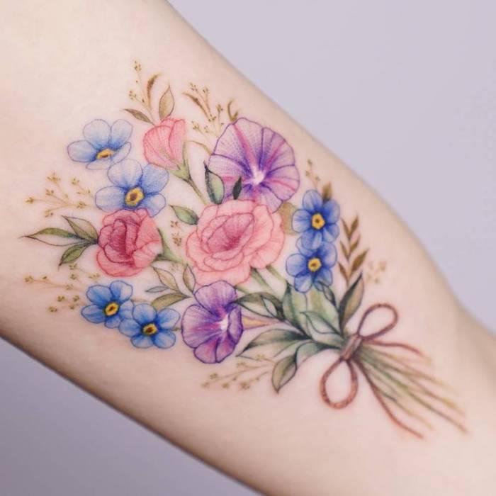 tatouage bouquet de fleur en rose et violet sur l avant bras