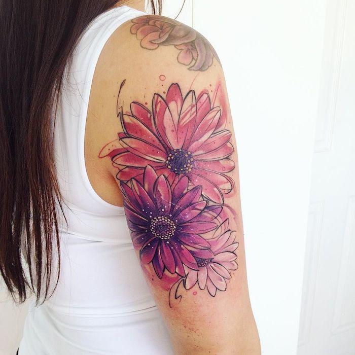 tatouage feminine sur l epaule avec un dessins des marguerites enormes en couleurs rose et violet